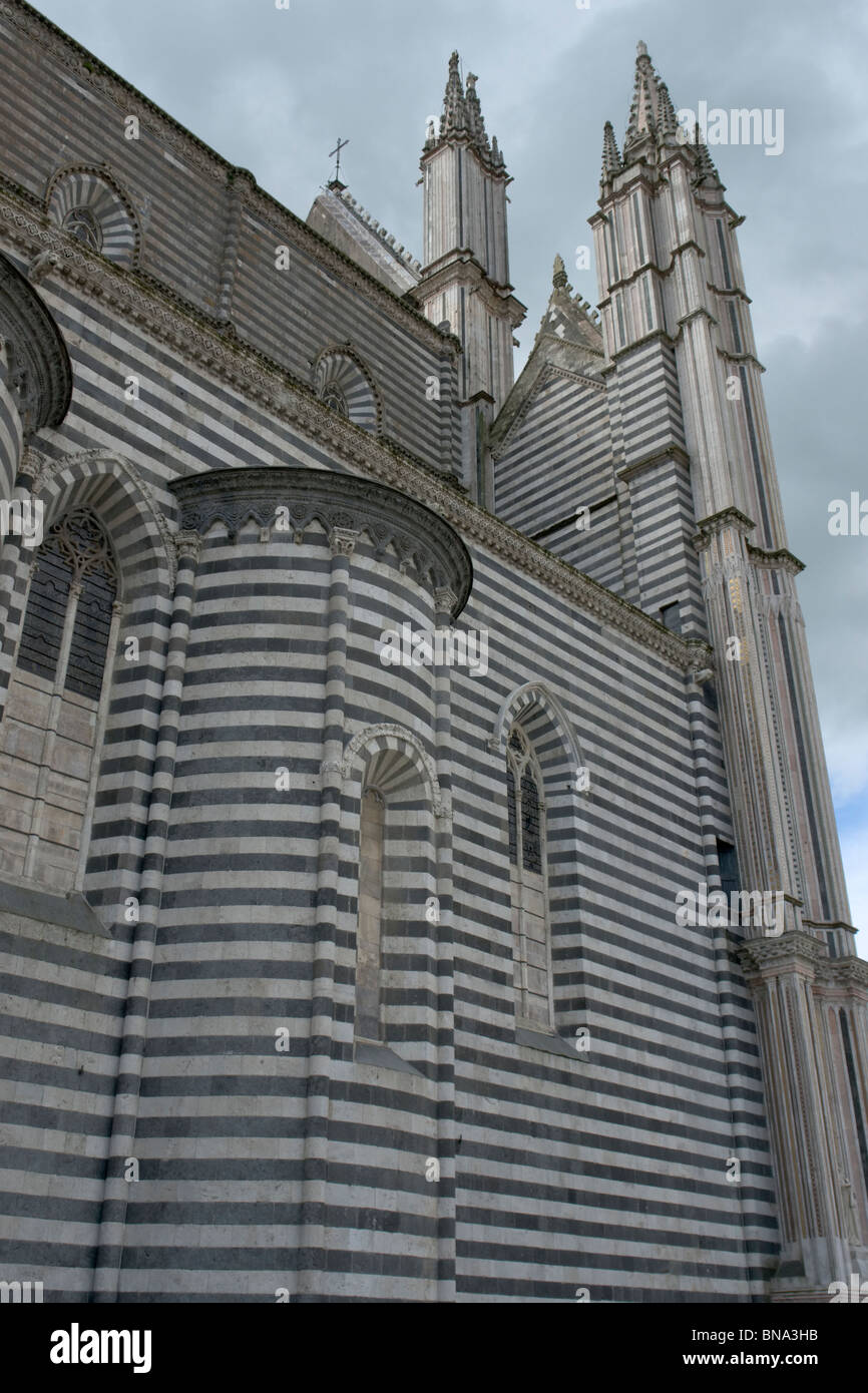 Orvieto, Italy. Side of the Duomo and back of the façade, in two-tone stones (travertine and basalt), with - Stock Image