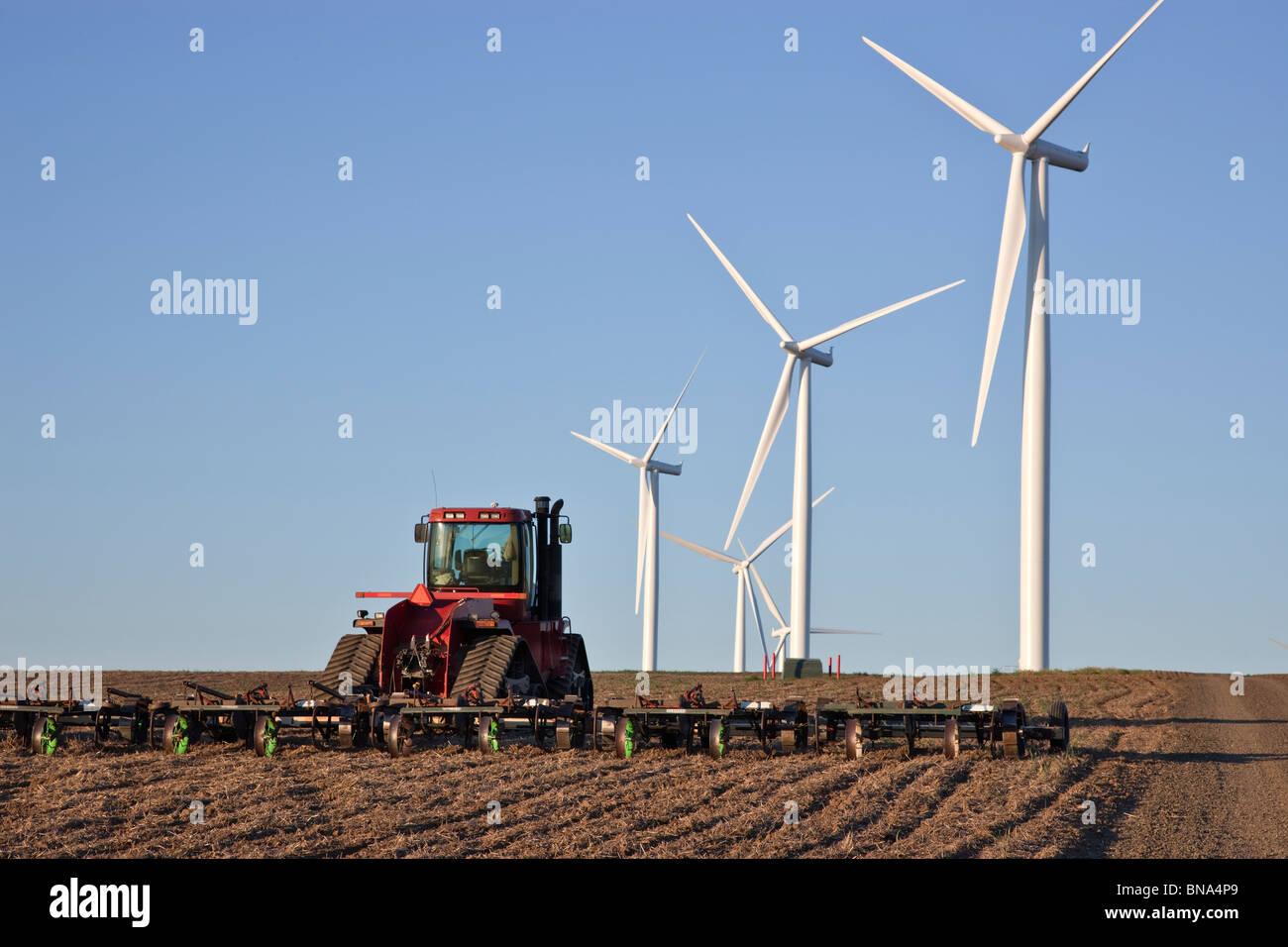 Tractor dragging harrow, fallow wheat field, wind farm. Stock Photo
