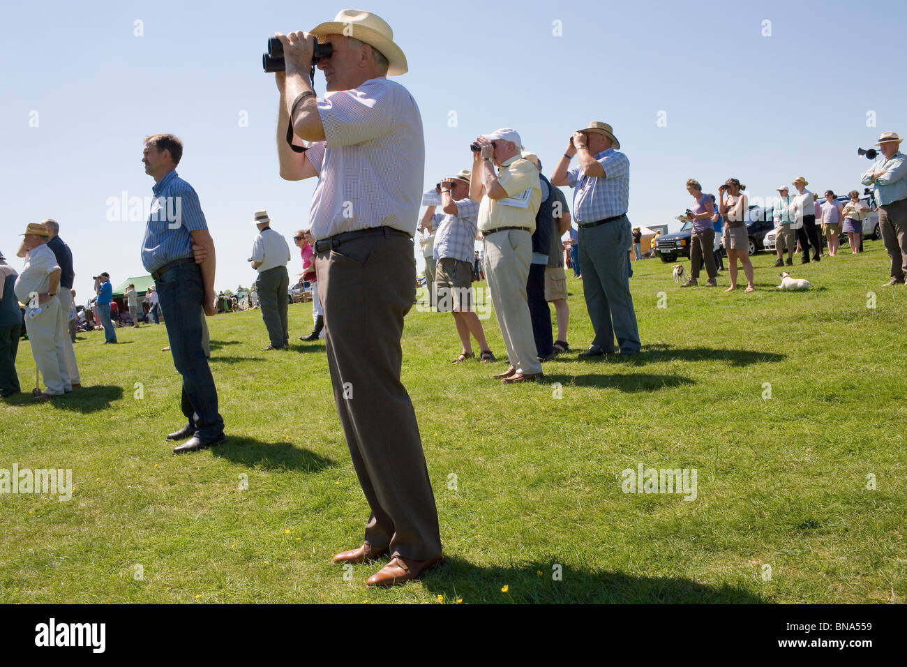 A man in a sun hat looks through a pair of binoculars on a hot summer day in the Engliah countryside. - Stock Image