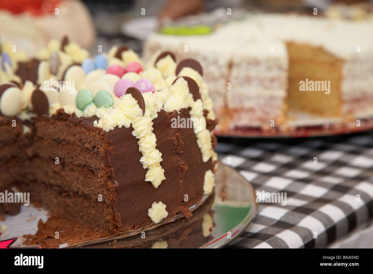large sliced chocolate cake cakes on table stall market in the uk - Stock Image