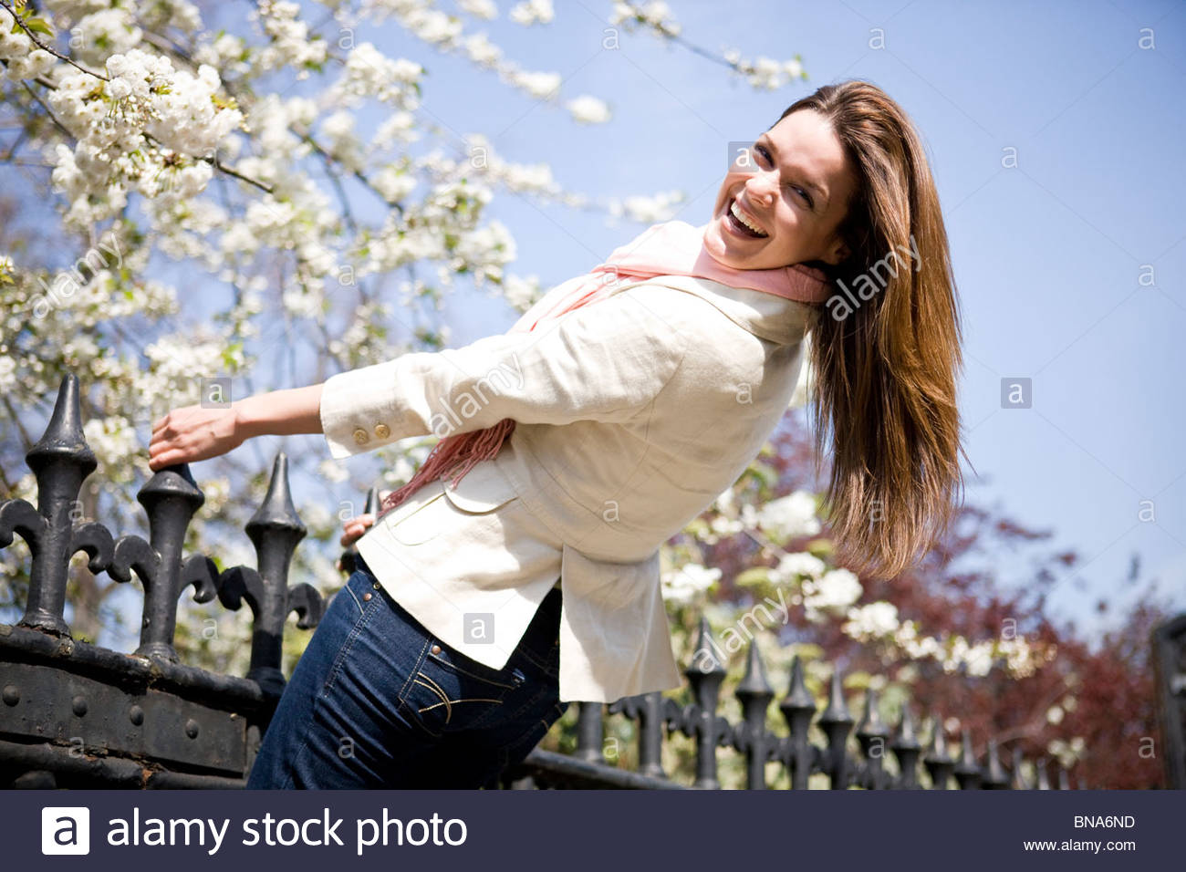 A young woman swinging on railings in springtime - Stock Image