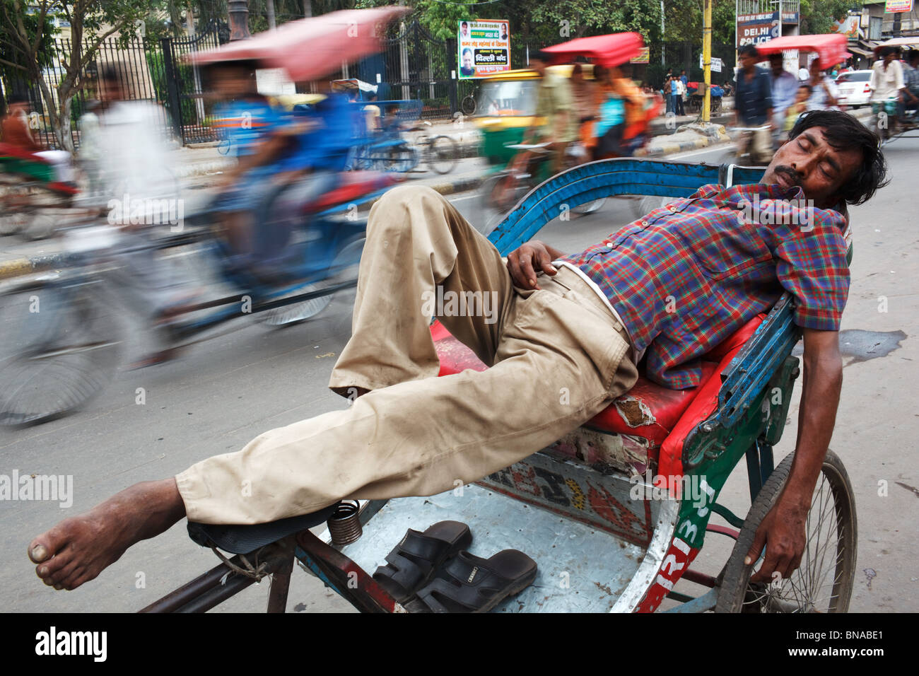 A rickshaw wallah naps on his rickshaw in the middle of the road in Chandni Chowk, Old Delhi, India - Stock Image
