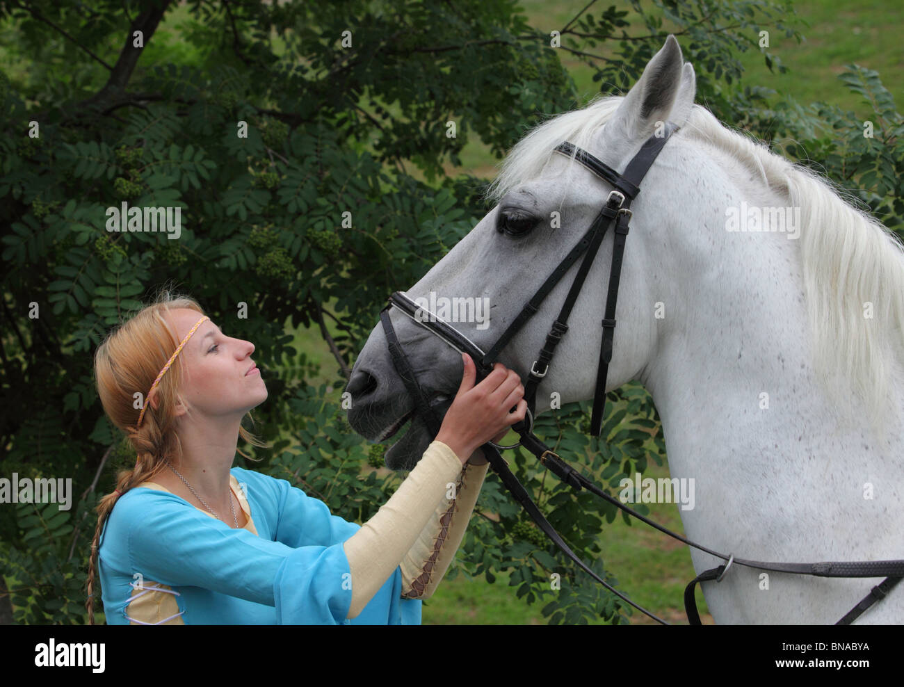 Slavic girl in Russian dress with her white horse - Stock Image