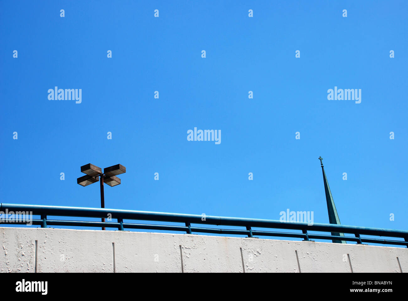 Parking garage with street lights on top and church steeple in background against clear blue sky. - Stock Image