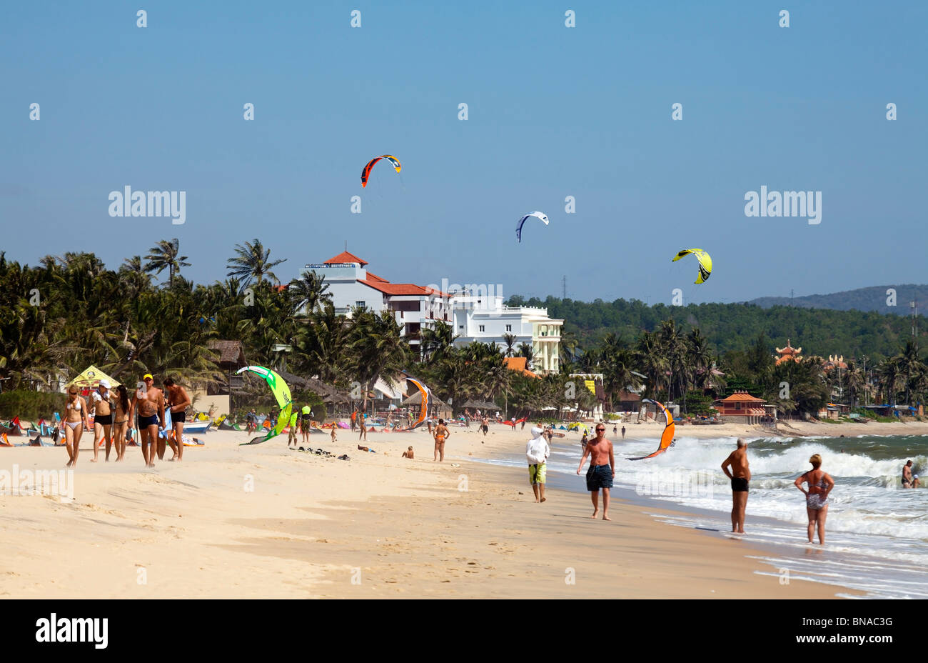 Main beach Mui Ne with tourists and kitesurfers - Stock Image