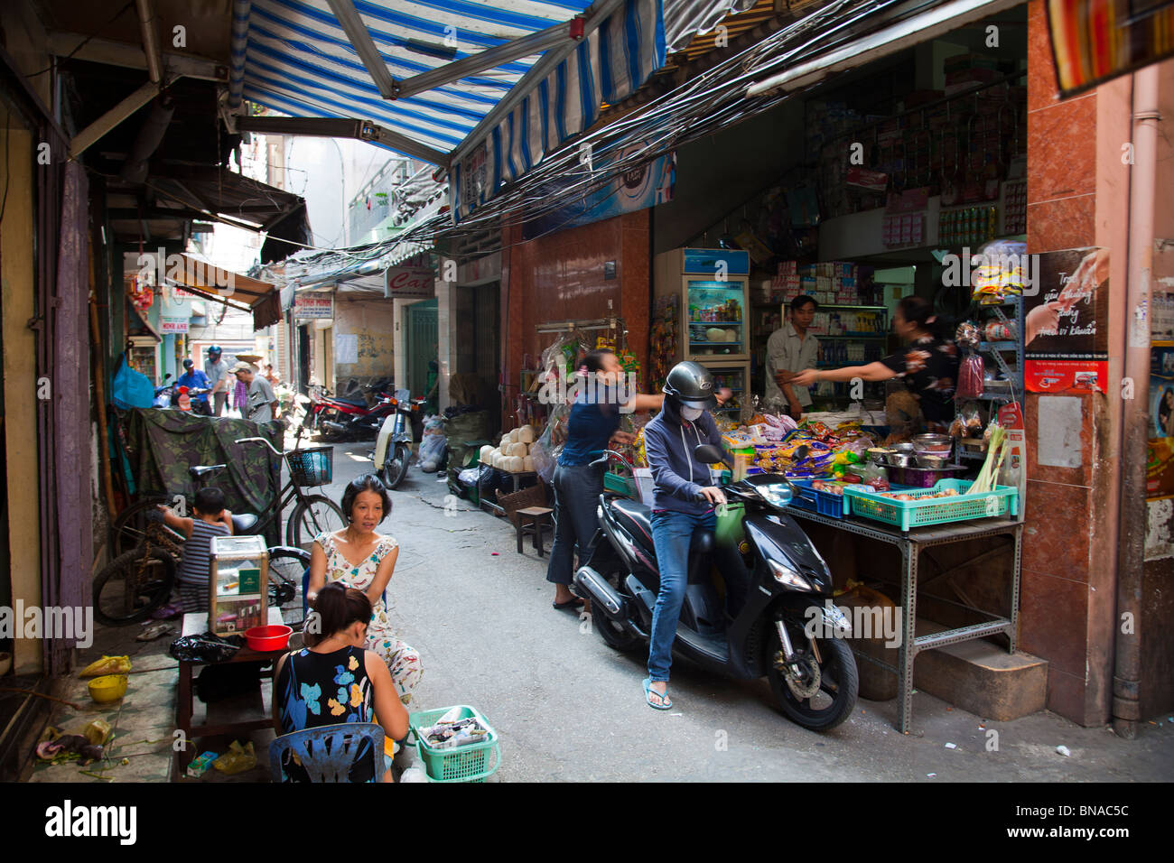 Busy lane with people and shops and restaurants - Stock Image