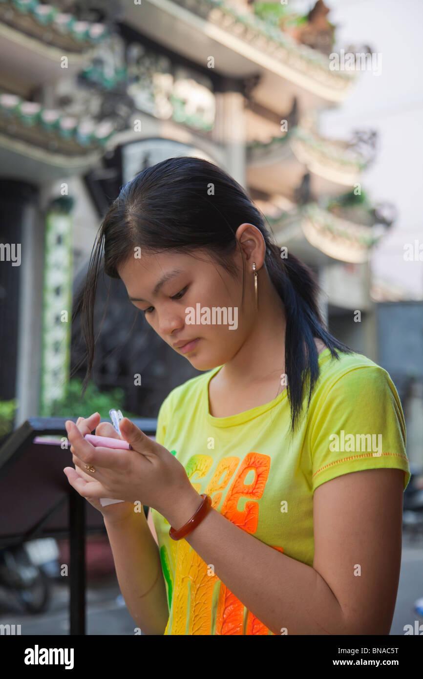 Young vietnamese waitress taking order - Stock Image