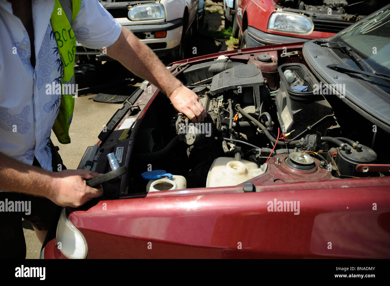Man removing a starter motor from car in breakers yard. - Stock Image