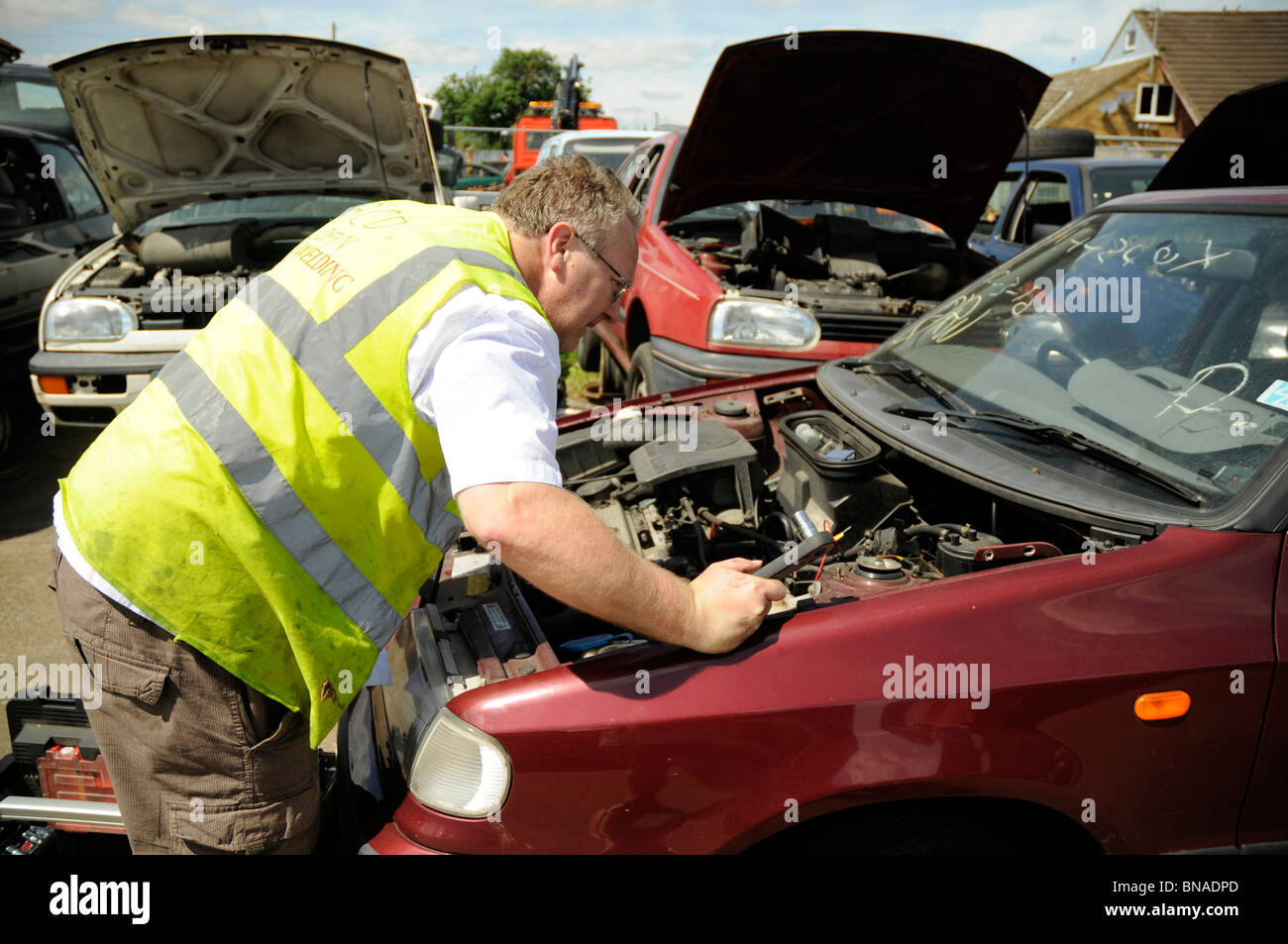 Man wearing hi-vis vest inspecting engine in a car in breakers yard. - Stock Image