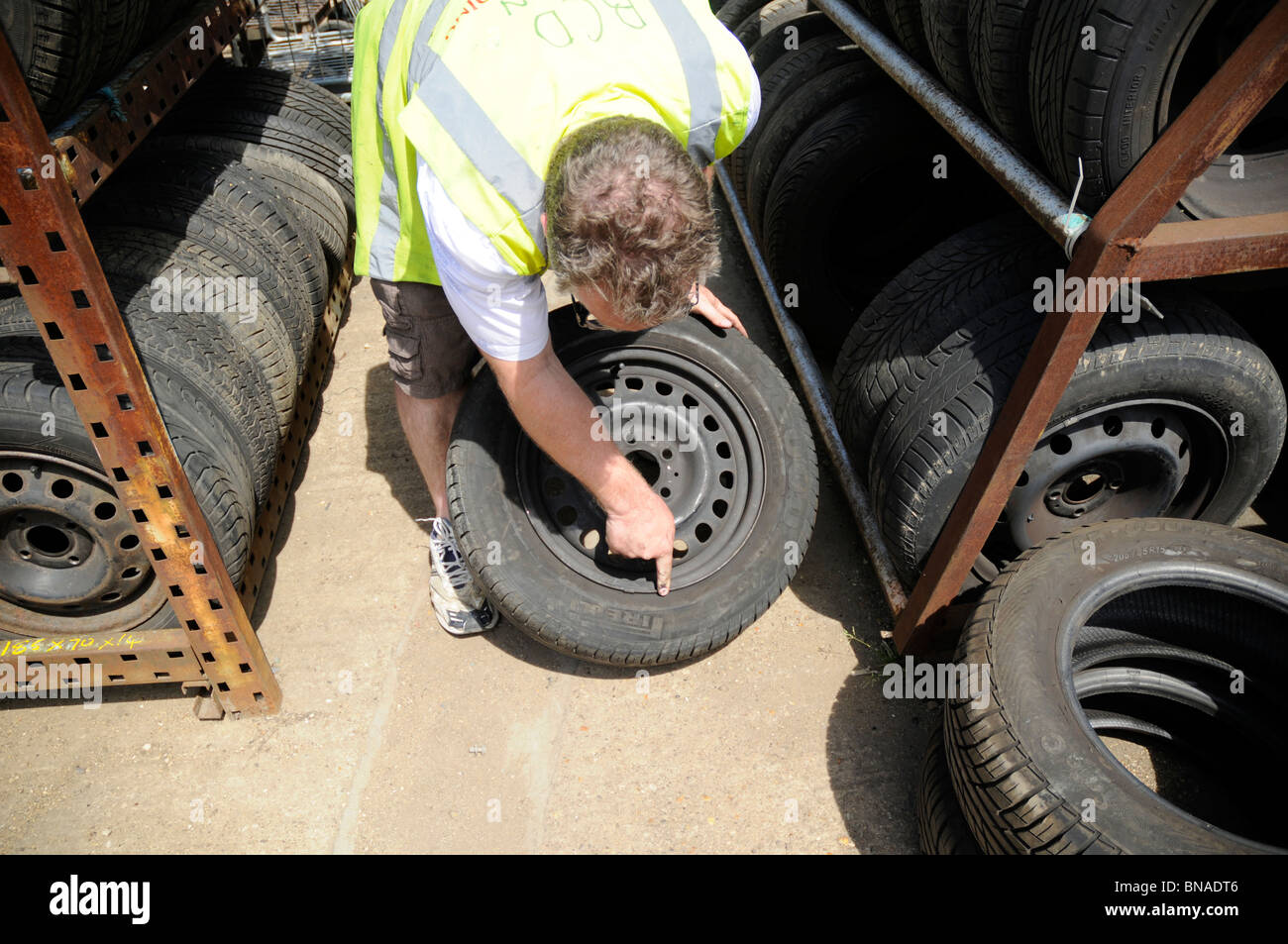 Man wearing hi-vis vest inspecting wheel and tyre in a car breakers yard. - Stock Image