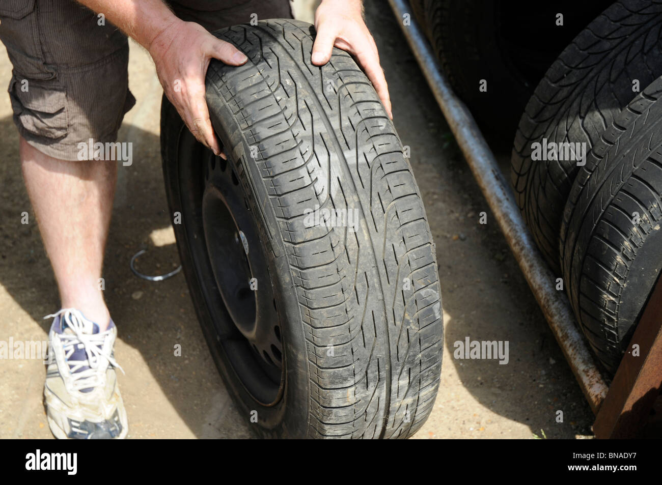 Man inspecting secondhand tyre in a car breakers yard. - Stock Image