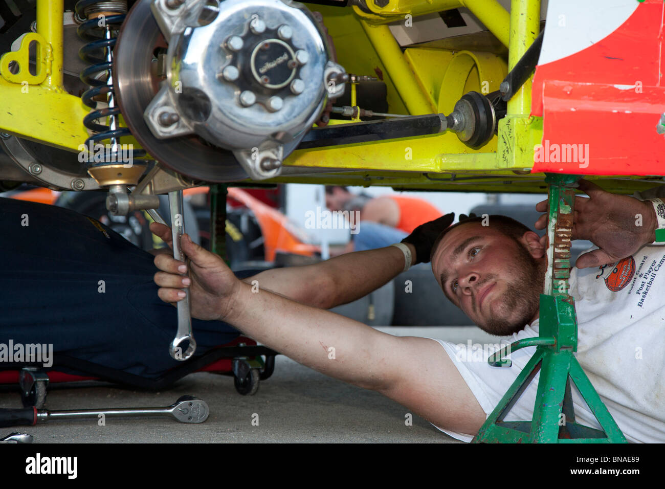 Woodstock, New Hampshire - A mechanic works on a car in the pits during stock car racing at White Mountain Motorsports - Stock Image