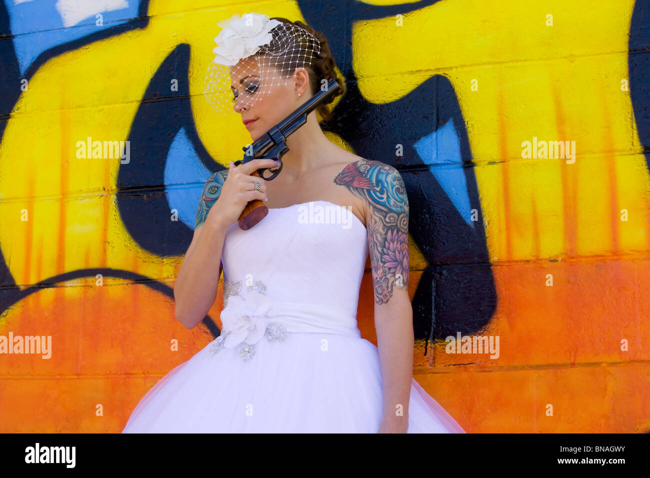 Tattooed bride against graffiti background with hand gun - Stock Image