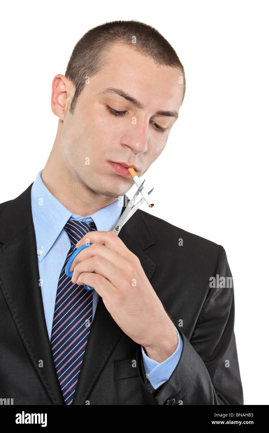 A man cutting a cigarette with scissors - Stock Image