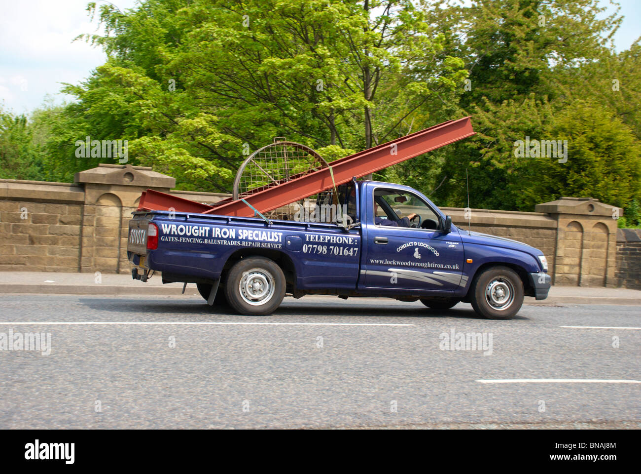 Pick-up truck carrying iron / steel products - Stock Image