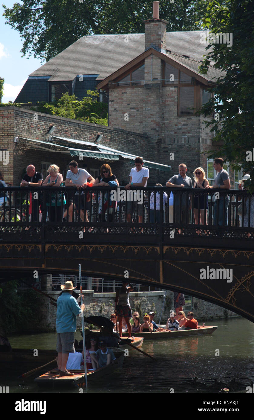Punts on the river Cam going under the bridge in Magdalene Street, Cambridge, England, in the summer. - Stock Image