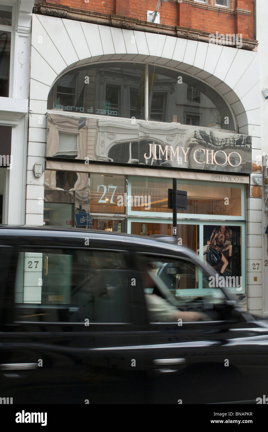 A Black Cab drives past the Jimmy Choo shoe shop in London. United Kingdom. - Stock Image