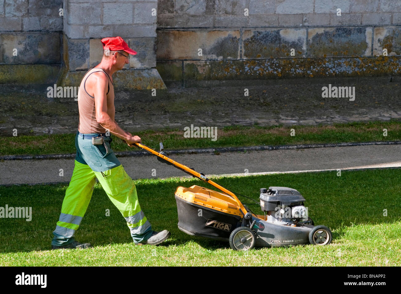 Town council workman mowing grass - France. - Stock Image