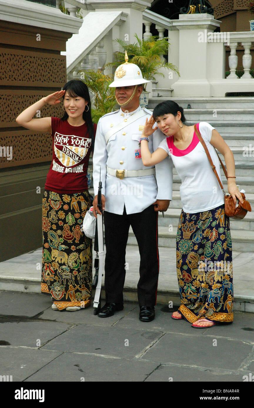 Good humoured Royal Guard poses with visitors to the Grand Palace Bangkok Thailand - Stock Image