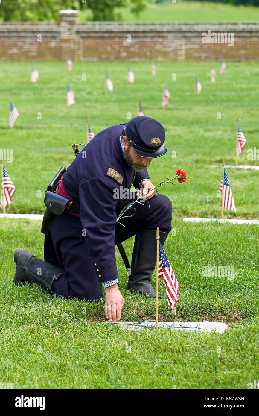 A Union Army reenactor pays his respects at the grave of a Civil War soldier in Yorktown National Cemetery in historic Stock Photo