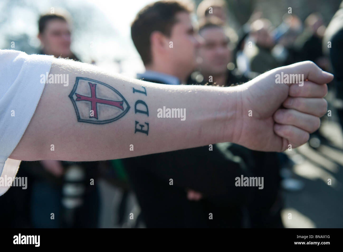 A member of the English Defence League  shows his EDL tattoo on his forearm - Stock Image