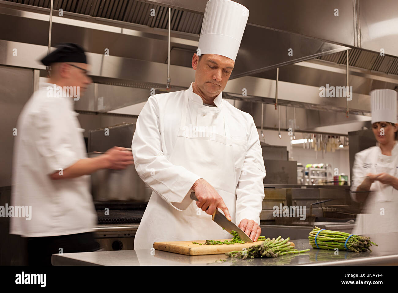 Chefs preparing food in commercial kitchen - Stock Image