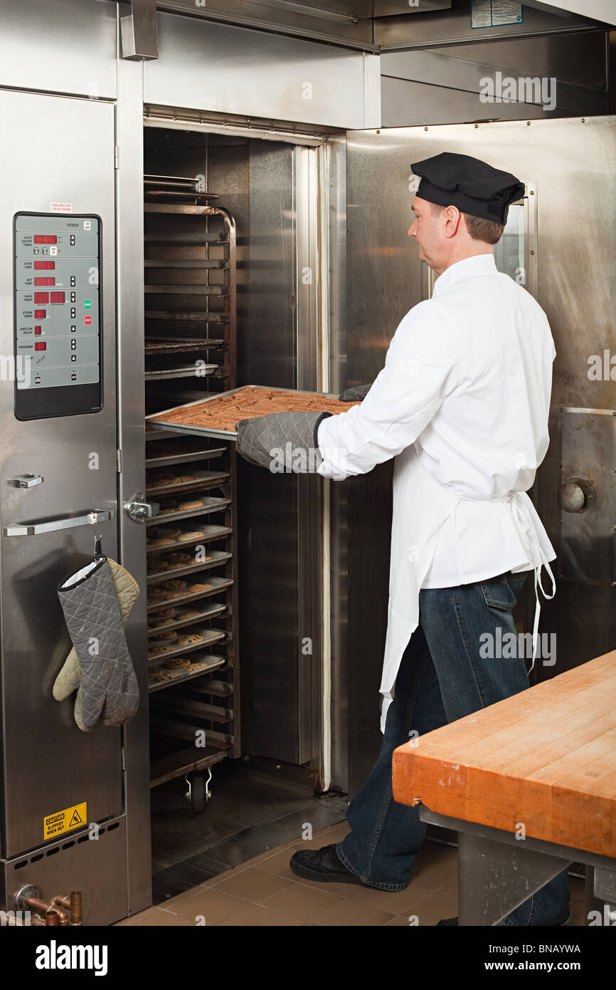 Male chef baking cookies in commercial kitchen - Stock Image