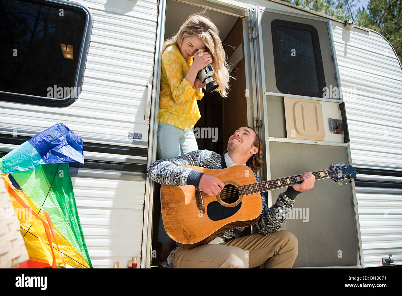 Young woman filming boyfriend playing the guitar - Stock Image