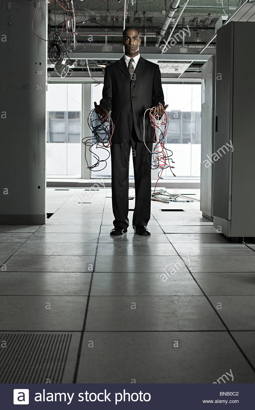 Businessman with cables in abandoned office - Stock Image