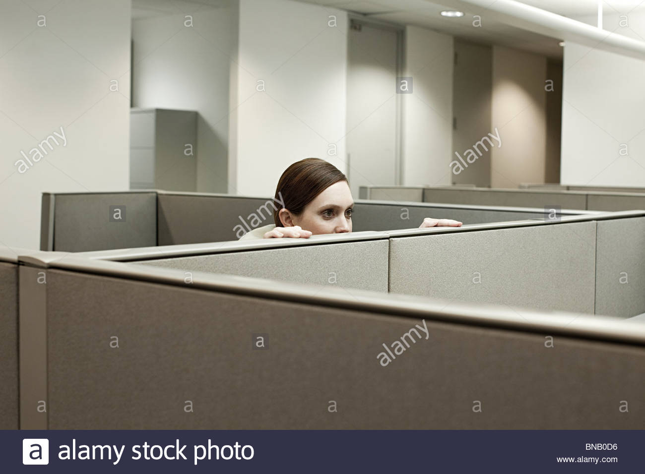 Woman hiding behind cubicle in office - Stock Image