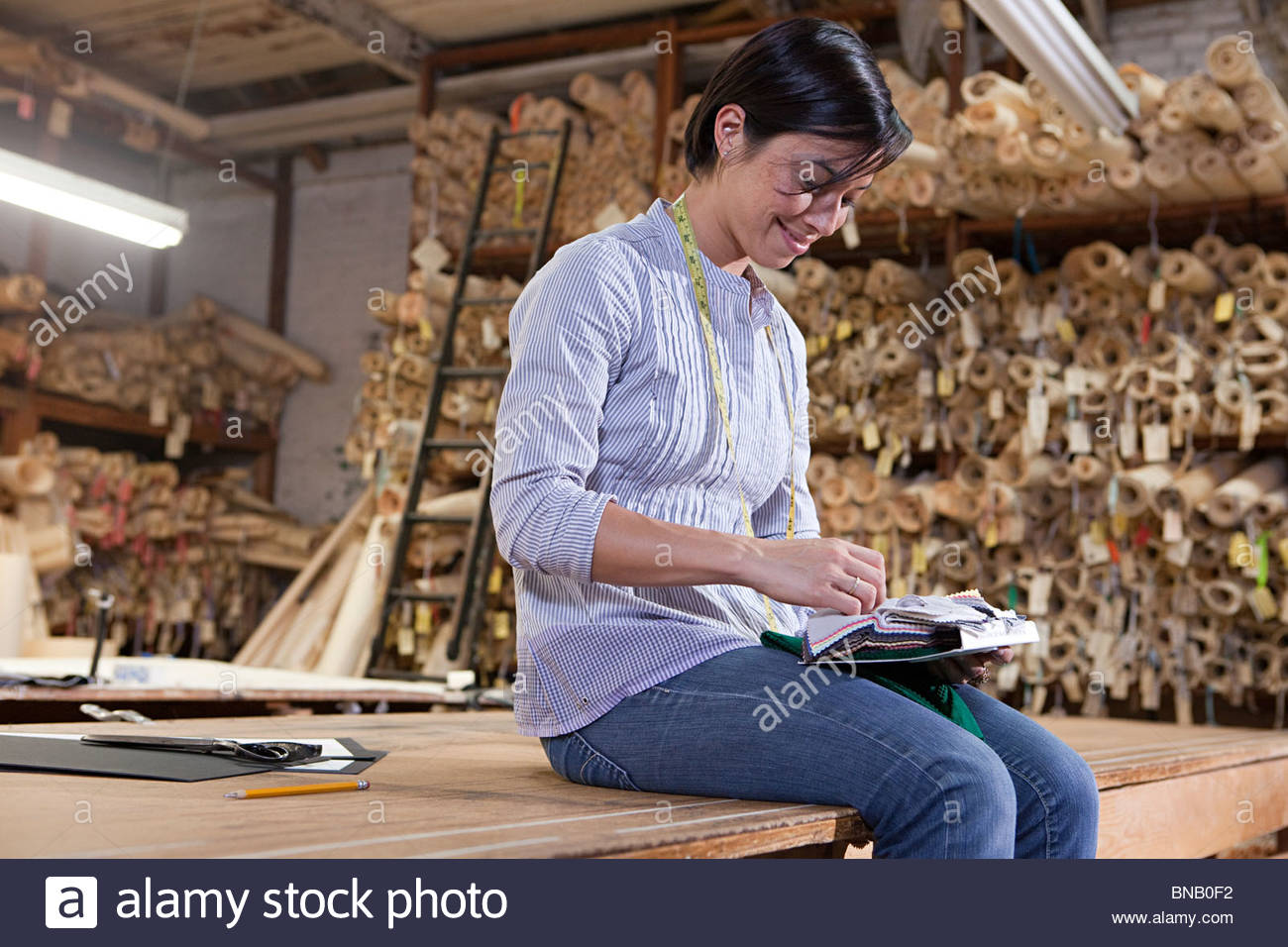 Tailor looking at fabric samples - Stock Image