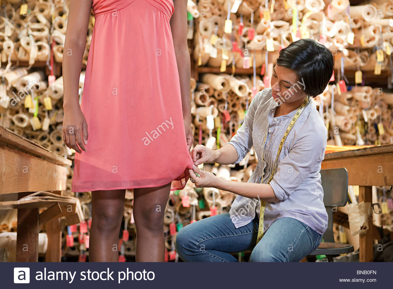 Seamstress adjusting dress on model - Stock Image