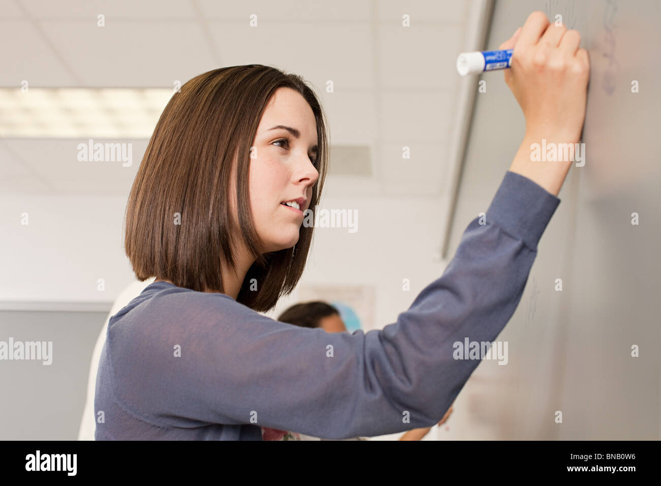 Female high school student writing on white board - Stock Image