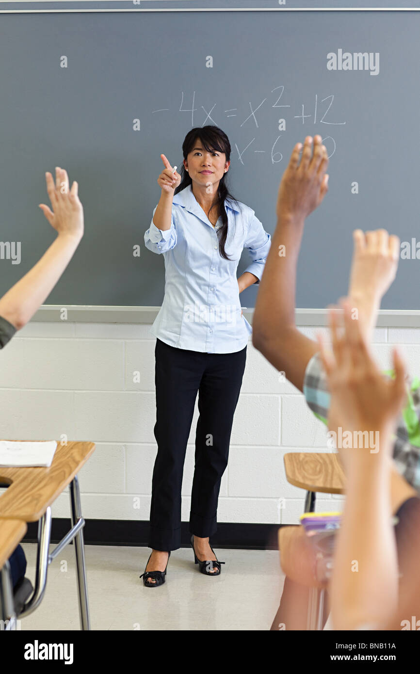 High school students with arms raised in classroom - Stock Image