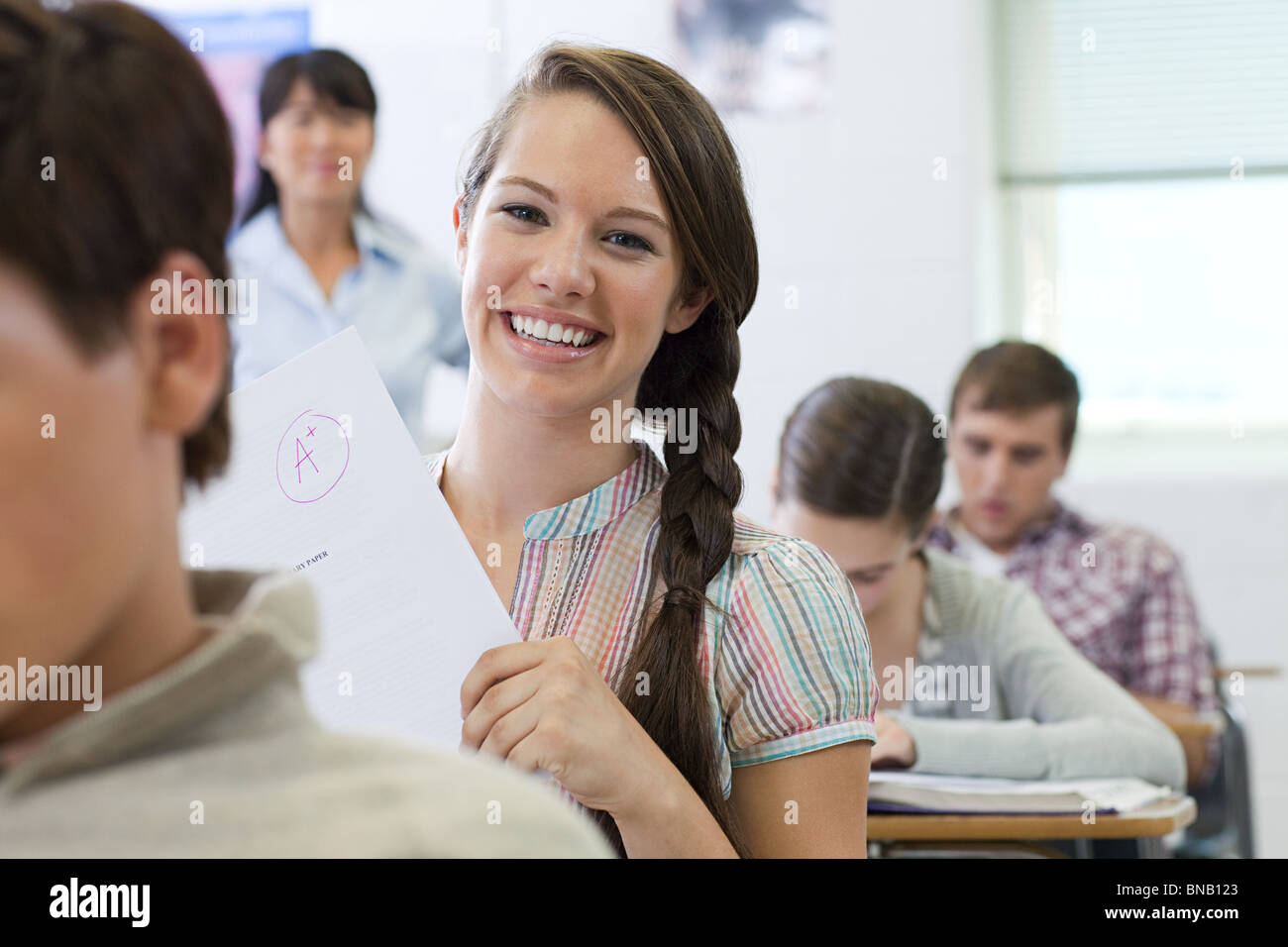 Successful female high school student holding assignment - Stock Image
