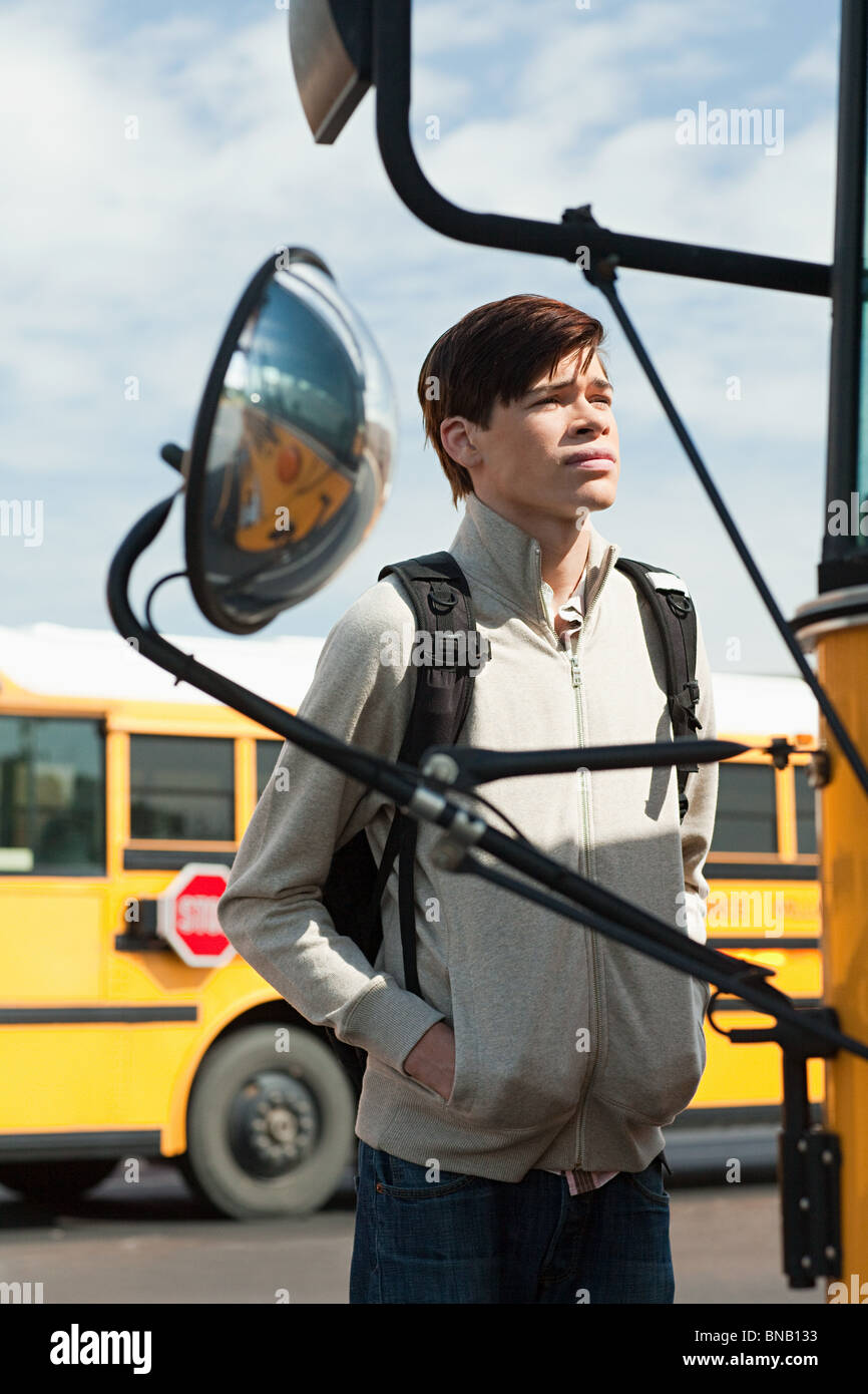 Male high school student standing outside school bus - Stock Image