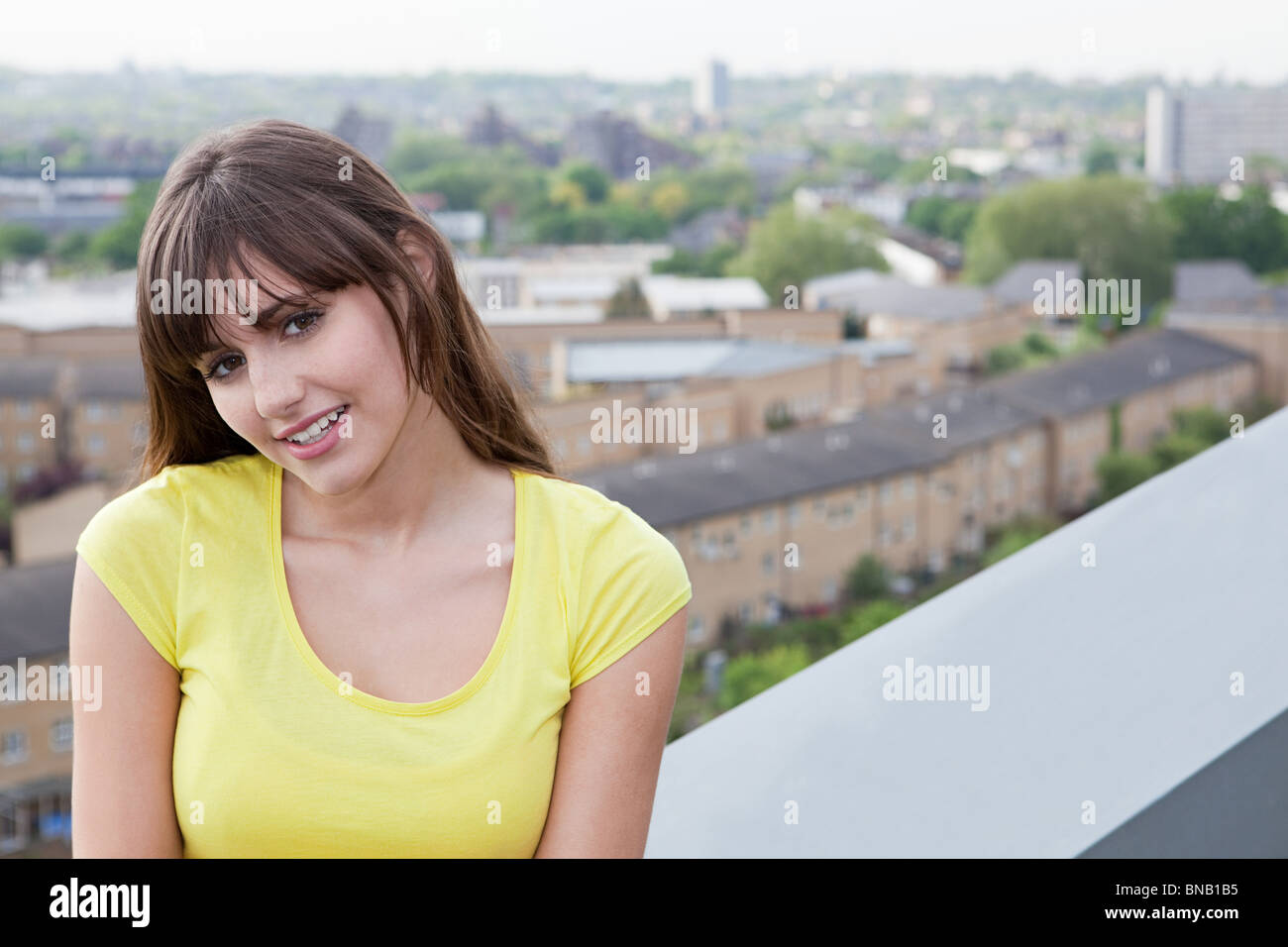 Young woman and urban scene in background - Stock Image
