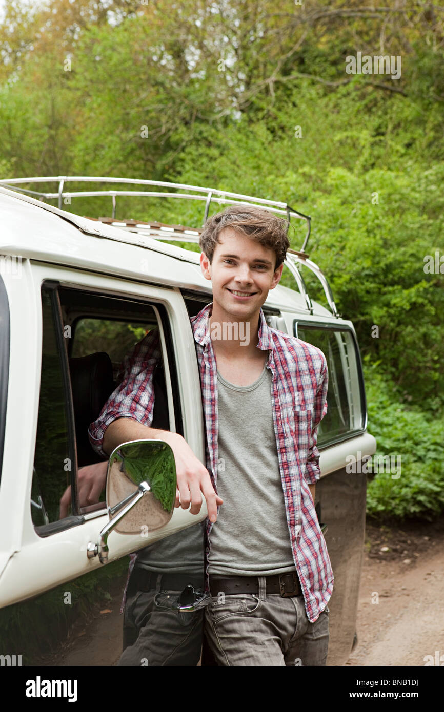Young man by camper van - Stock Image
