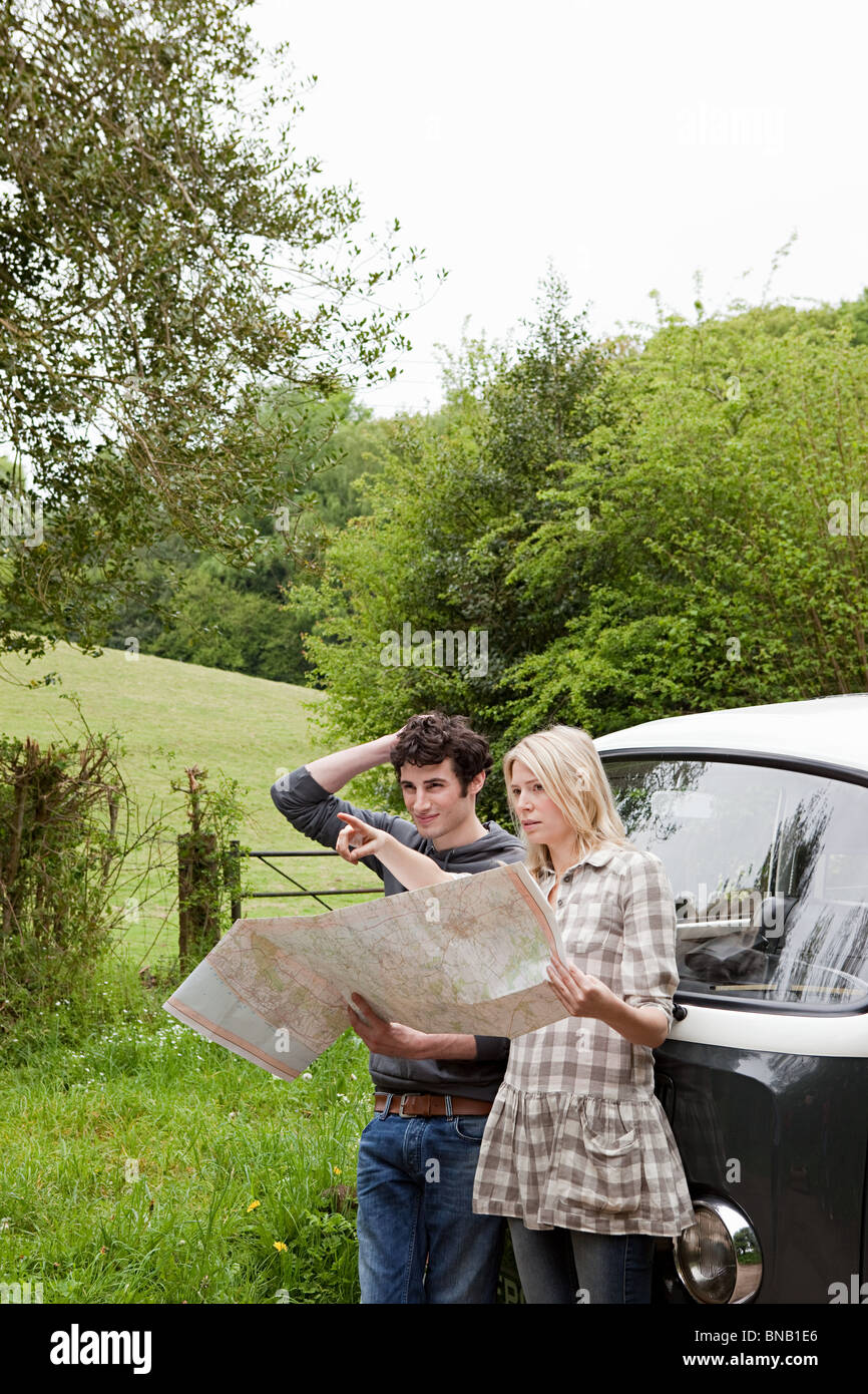 Young couple by camper van looking at map - Stock Image