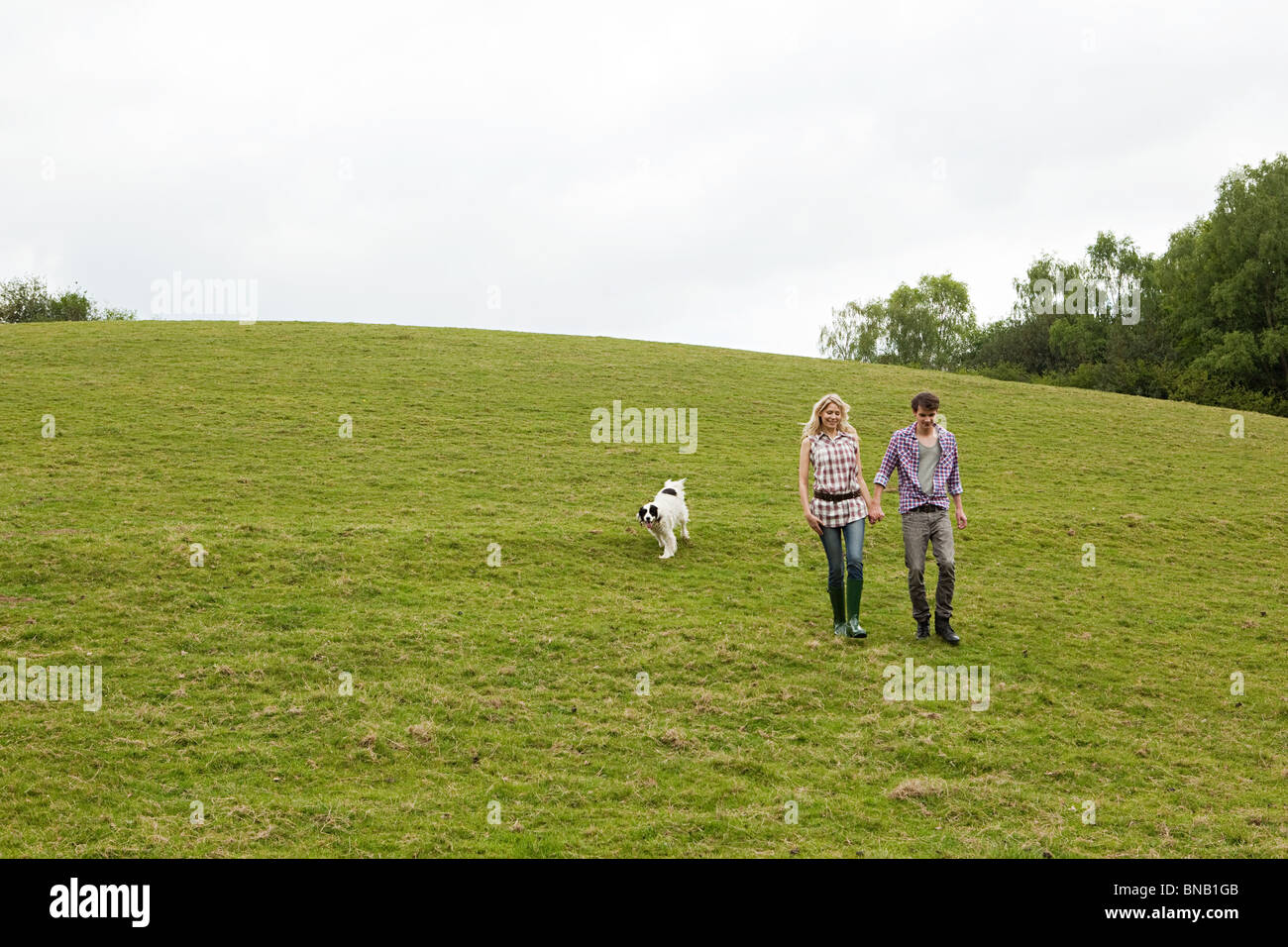 Young couple walking down hill with dog - Stock Image