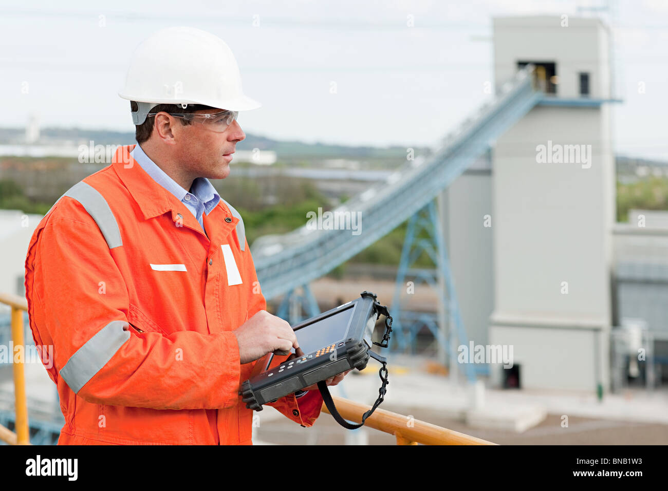 Engineer with handheld computer - Stock Image