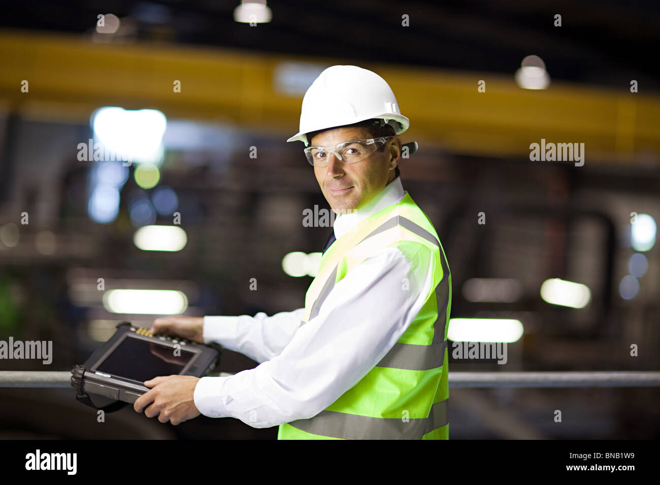 Engineer with handheld computer - Stock Image