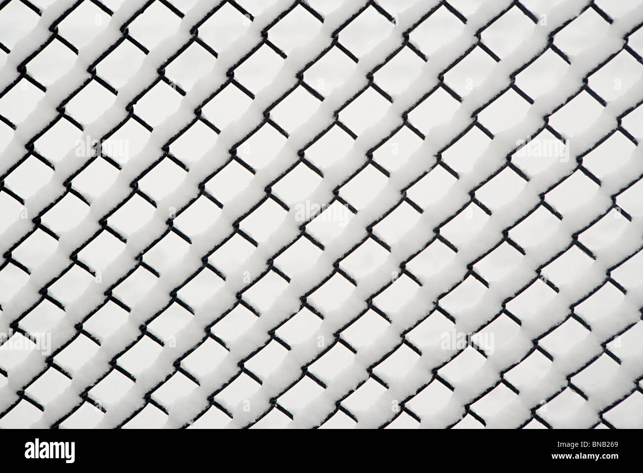 Snow on a chain link fence Stock Photo