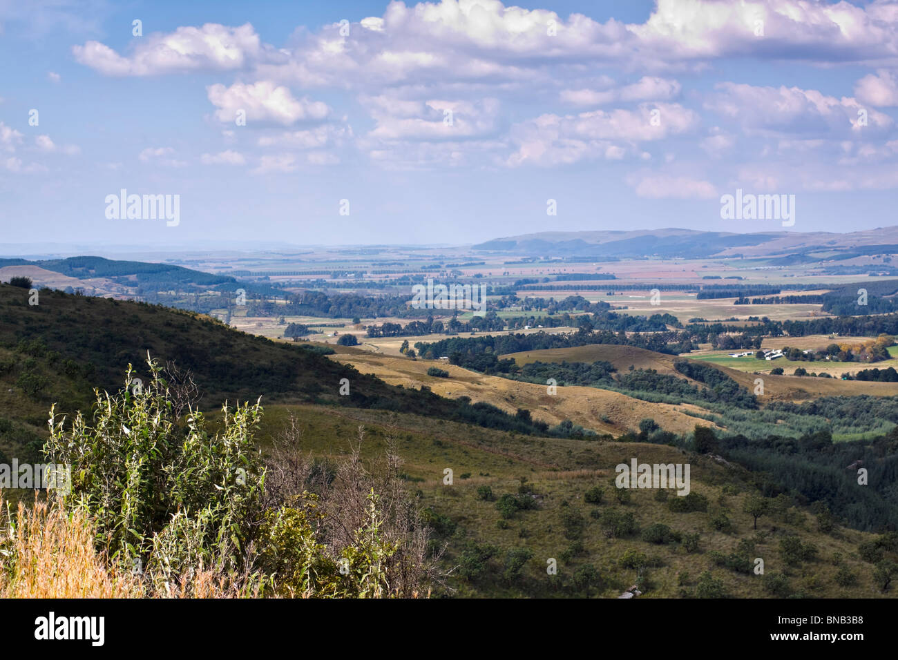 Distant farmlands in the foothills of the Drakensberg, Midlands, KwaZulu Natal, South Africa. Stock Photo