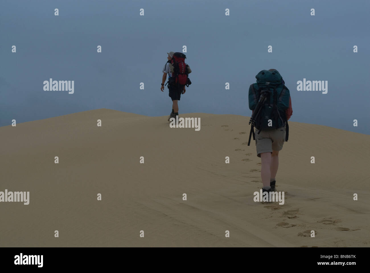 Low angle of two trekkers walking the crest of a hill with their backpacks, against the blue of the sky. Footprints - Stock Image