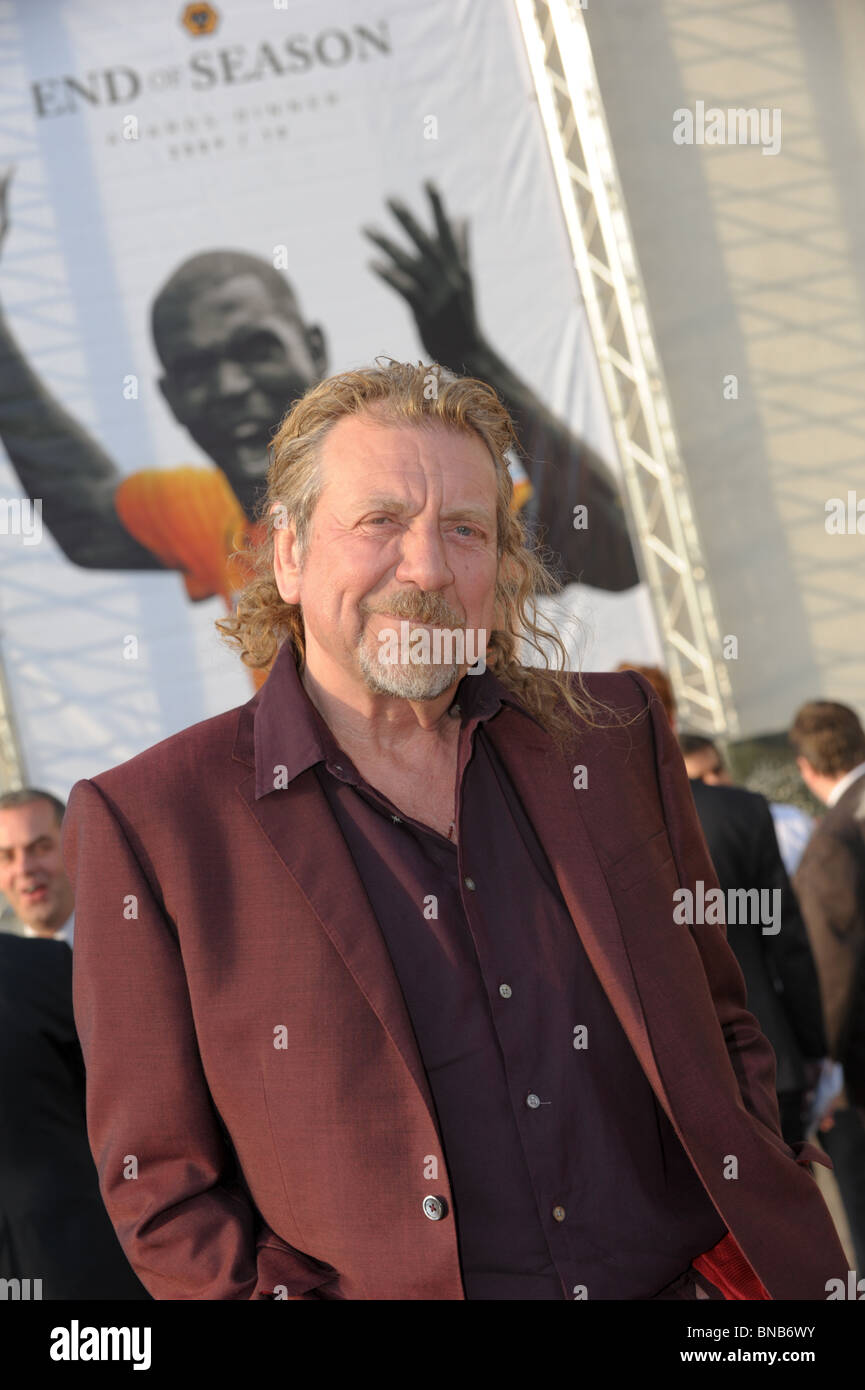 Led Zeppelin's Robert Plant stands infront of  Wolves FC end of season 2010 poster featuring striker Sylvan - Stock Image