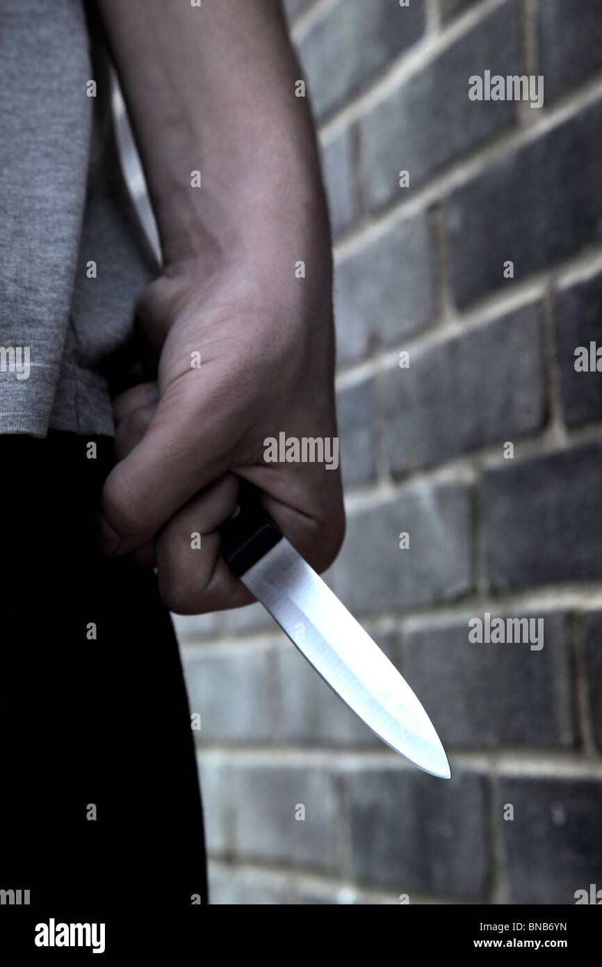Hand of a young male holding a knife walking past a brick wall Stock Photo
