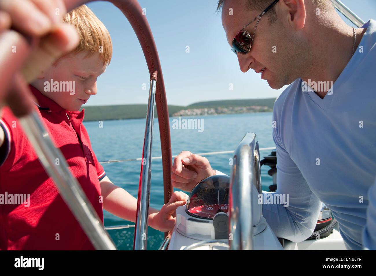 Man explaining boy compass on yacht - Stock Image