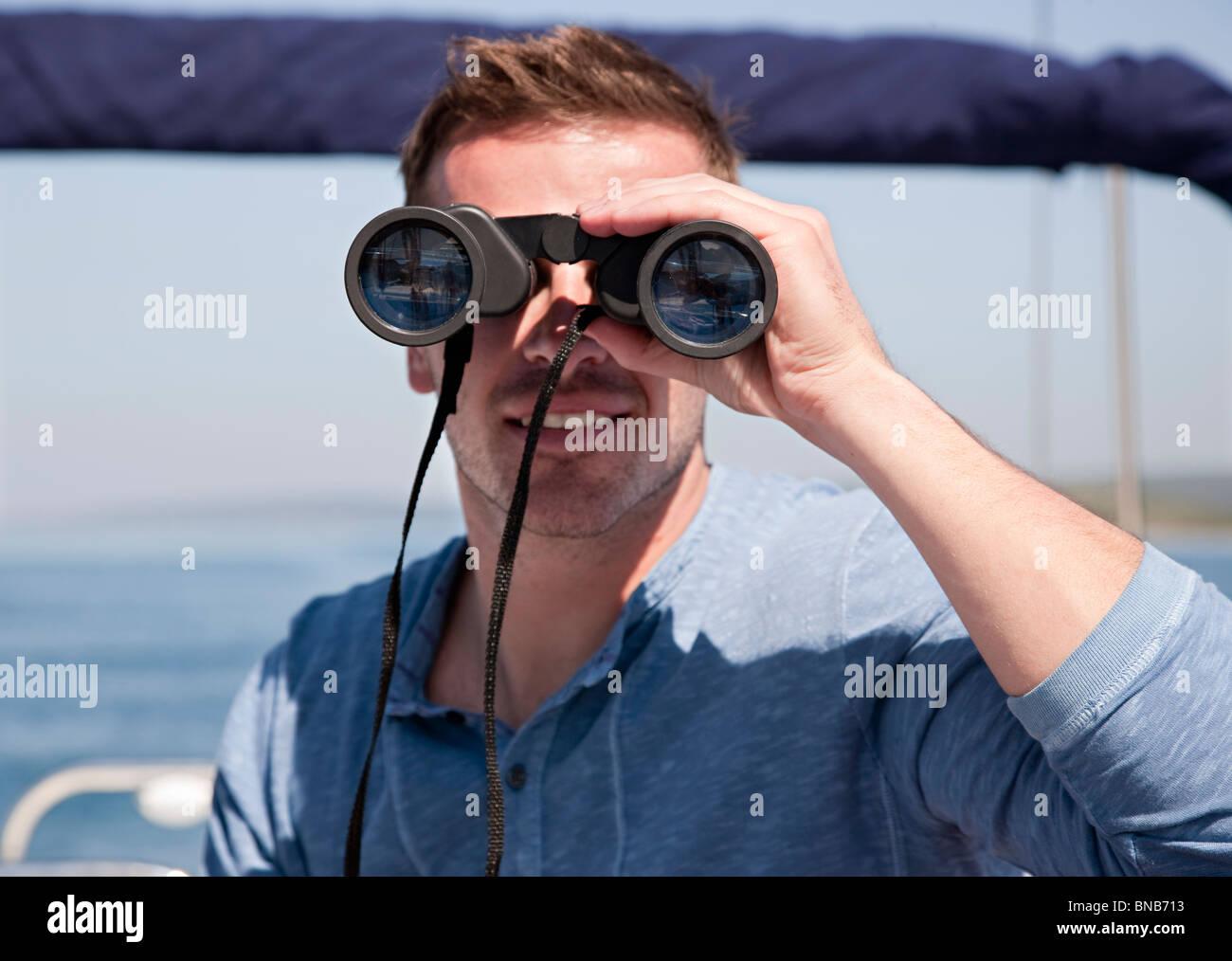 Man with binoculars on yacht - Stock Image
