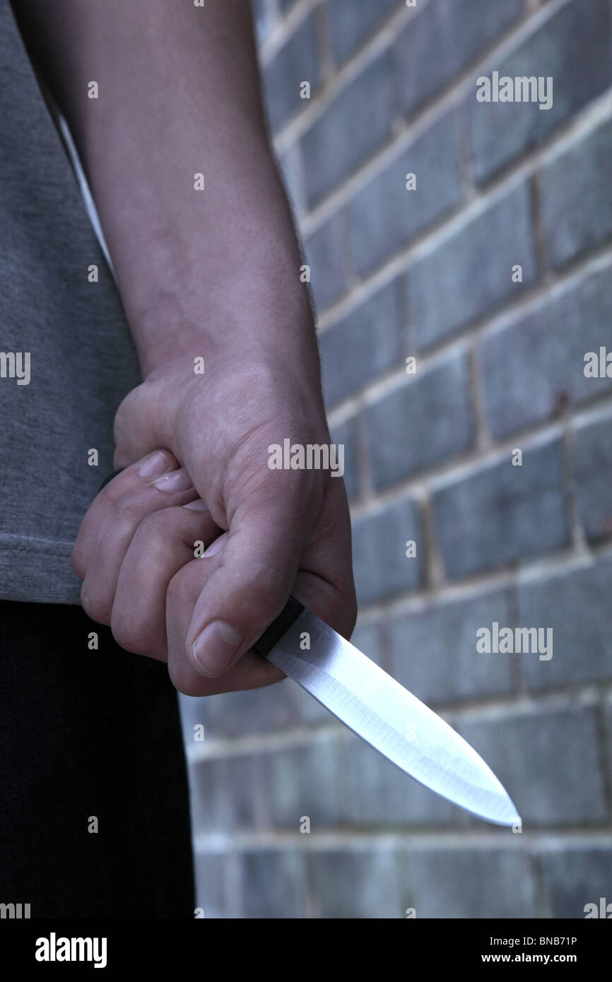 Hand of a young male holding a knife walking past a brick wall - Stock Image